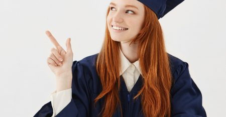 Young female university graduate in academic cap sitting at table smiling pointing left. Future lawyer or engineer showing an idea. White background.